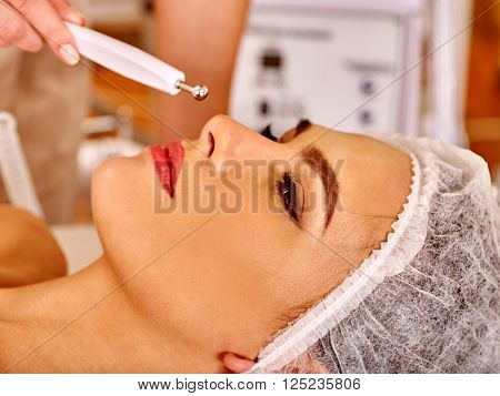Close up of  young woman receiving electric facial eyes massage on microdermabrasion equipment at beauty salon.  poster
