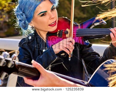 Music street performers girl with blue hair violinist  playing  aganist sky with clouds outdoor. The second girl - violinist with her.