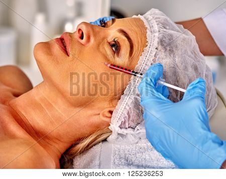 Relaxed woman middle-aged in spa salon with beautician. Beauty woman giving rejuvenating injections.