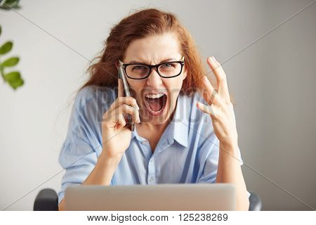 Portrait Of A Young Irritated Businesswoman Wearing Glasses And Shirt Looking With Anger At The Came