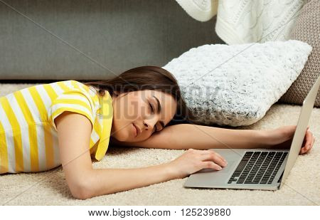 Young woman fell asleep at the laptop on the floor
