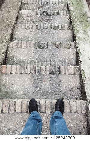 Male Feet In Blue Jeans On Old Stone Stairs
