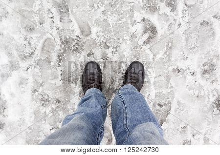 Male Feet In Blue Jeans Standing On Wet Snow