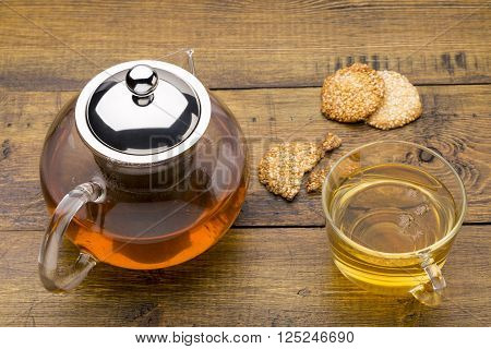 Glass cup of green tea and teapot with sesame cookies on wooden background