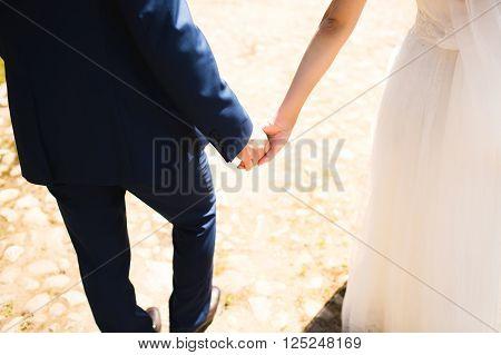 wedding theme holding hands newlyweds walking sunny summer day
