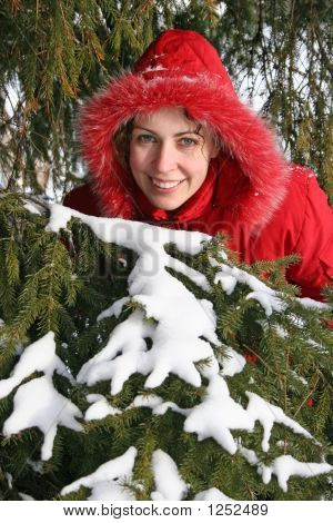 Smiling Woman Behind Snowy Tree