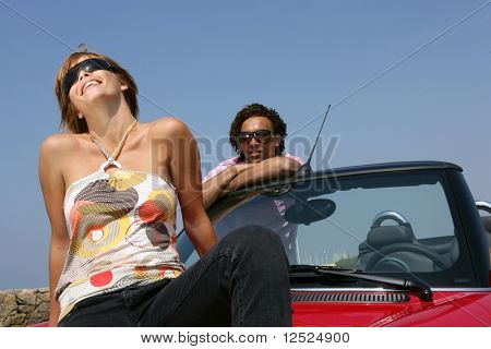 Couple sitting on a red carhood