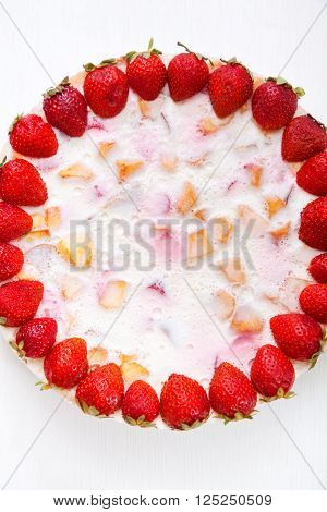 Cake with strawberries gelly yogurt and cherries. Surface view. Isolated on white background.
