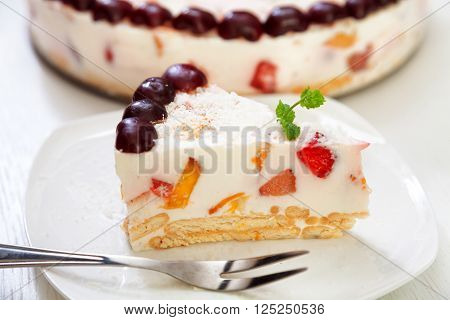 Cake with cherris gelly yogurt and fruits. Isolated on white background. One piece in a white plate. Horizonta; shot ** Note: Shallow depth of field