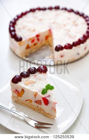 Cake with cherris gelly yogurt and fruits. Isolated on white background. One piece in a white plate. Vertical shot ** Note: Shallow depth of field