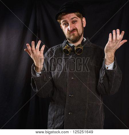 dissatisfied welder in black boilersuit in studio