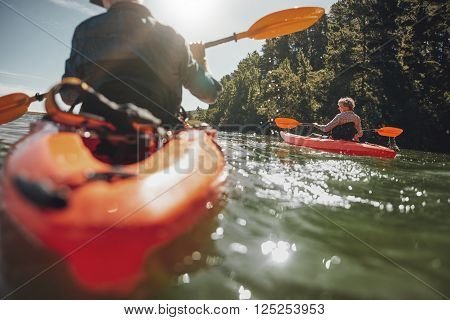 Portrait of mature woman kayaking in lake on a sunny day. Couple canoeing in a lake on  summer day.