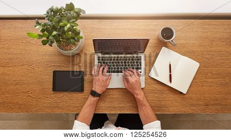 Directly above view of human hands typing on laptop. Laptop, digital tablet, diary, coffee cup and potted plant on work desk. Man working from home.