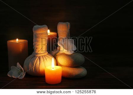 Spa composition with alight candles on wooden background in the dark