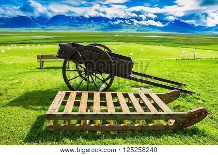 Old wooden sledge and two-wheeled cart on the lawn. The reconstituted village -  Museum Vikings in Iceland