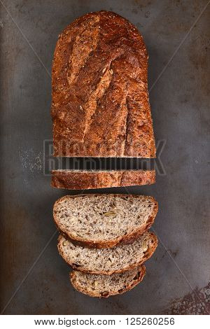 Top view of a loaf of multi-grain bread on a baking sheet. The loaf is partially sliced,