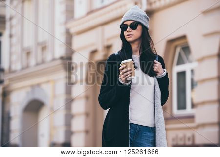 Urban girl. Beautiful young woman holding coffee cup and looking away while walking outdoors