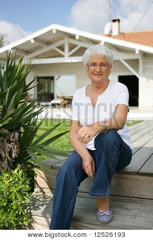 Senior woman sitting in front yard