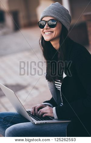 Modern blogger. Side view of beautiful young woman using her laptop and looking away with smile while sitting outdoors