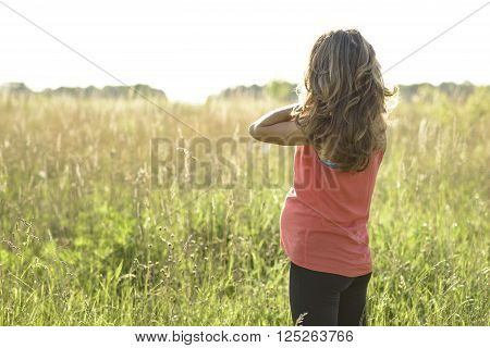 Pregnant girl standing in a field straightens hair, a bright sunny day a woman waiting for a child. In the meadow in a red dress with long hair.