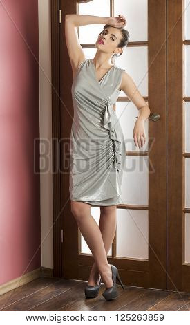 indoor fashion portrait of elegant brunette girl with silver dress hairdo and make-up. She is looking in camera