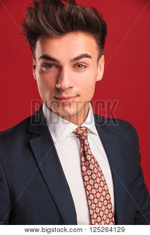 closeup portrait of attractive young businessman in black suit with red tie, posing in red studio background while looking at the camera