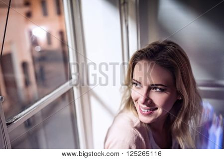 Beautiful blond woman sitting on window sill at night, looking out of window, smiling