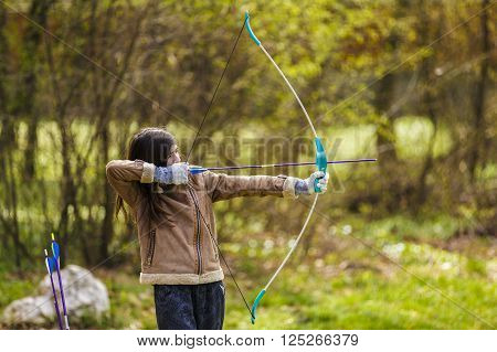 girl archer shooting with his bow at an outdoor archery range