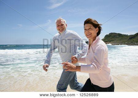 Senior couple running on the beach