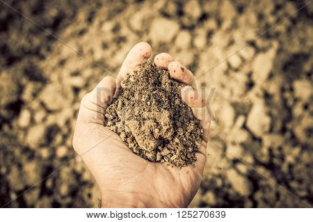 dry soil in the hand - dryness concept