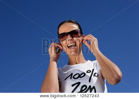 Portrait of a smiling woman with a mp3 walkman and sunglasses