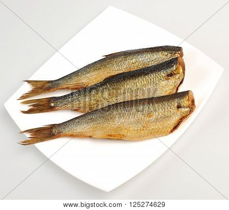 three smoked fish without head on a plate