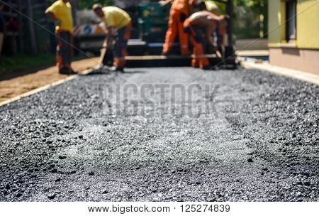 Team of Workers making and constructing asphalt road construction with finisher. The top layer of asphalt road on a private residence house driveway