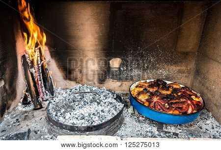 Preparing and Cooking of octopus and chicken in traditional Croatian or Greek meal Peka in metal pots called sac or sach with a lid. Traditional roast of octopus and chicken with potatoes onions garlic tomato and spices.