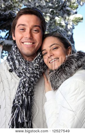 Portrait of smiling man and woman at the snow