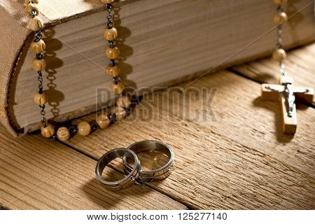 detail of weddings rings bible and prayer beads
