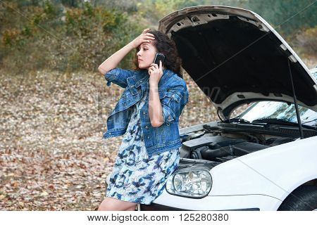 girl with a broken car, open the hood, call for help