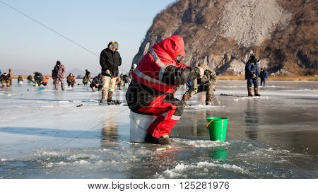 Fishermen catch smelt in the winter on the river. Primorsky Krai, Far East Russia.
