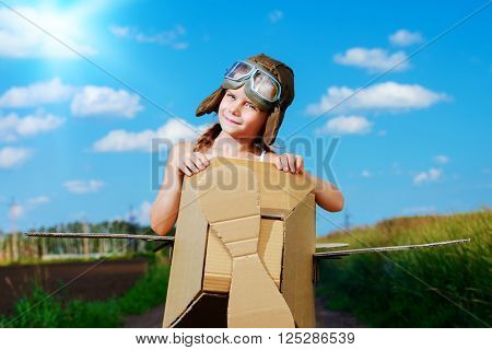 Little dreamer girl playing with a cardboard airplane in the field over blue sky and white clouds. Childhood. Fantasy, imagination.