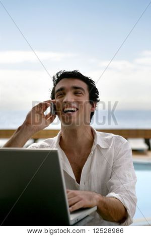 Portrait of a man phoning in front of a laptop computer