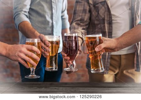 Male group clinking glasses of dark and light beer at the table