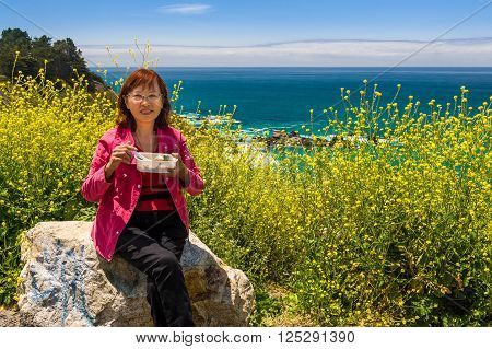 Happy Asian senior on travel enjoying meal with beautiful scenery background with flowers in bloom.