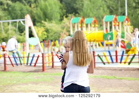 Touchy little boy in the arms of his mother in summer park