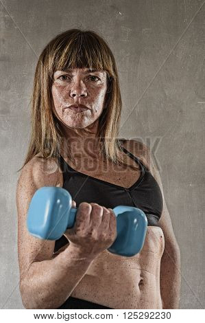 40s fit and strong sport freckles woman holding weight on her hand posing defiant in cool attitude with welt built body in gym club harsh light advertising style