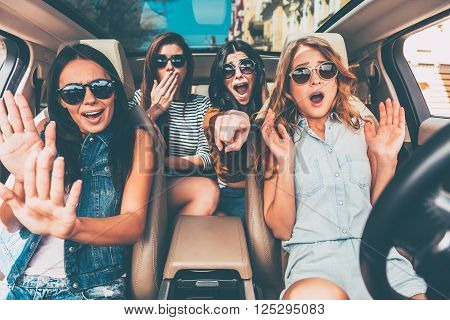 Stop! Four young women gesturing and looking terrified while sitting in car together