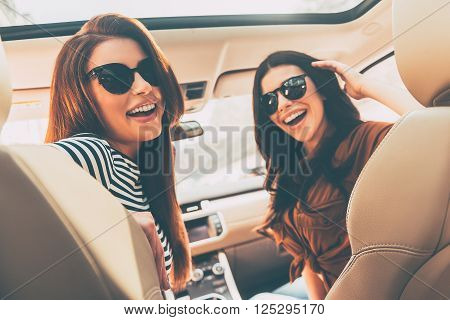 Ready to road trip! Rear view of two beautiful young cheerful women looking at camera with smile while sitting in car