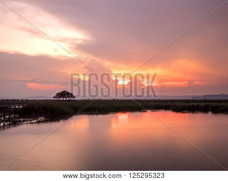 Beauty landscape with sunset under the sky with wooden bridge and pavilion on the river at Thailand (Sam Roi Yot Freshwater Marsh)