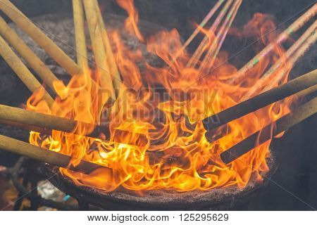Lighting up the joss stick with fire flames. Asian traditional religion for the Good luck.