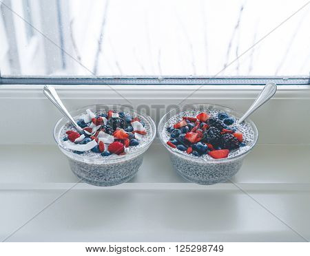 Vanilla chia seed puddings for two with berries, coconut and goji Berries. A trendy, delicious and healthy snack.