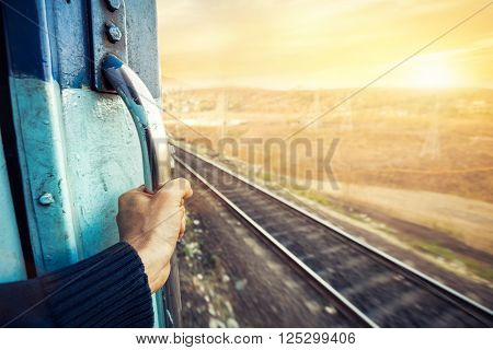 Man in the train passing desert area at sunset sky background in Rajasthan India